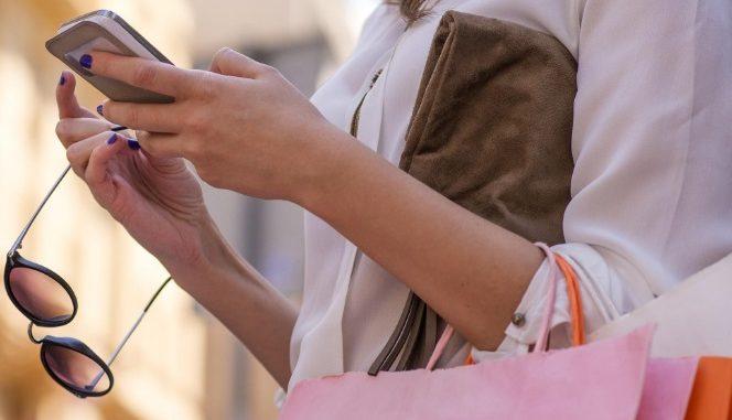 Femme avec sacs de shopping et smartphone