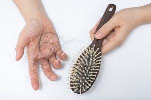 Brosse à cheveux et main avec des cheveux