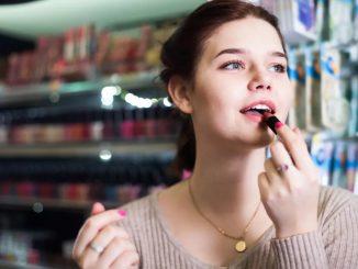 Femme qui se met du rouge à lèvre