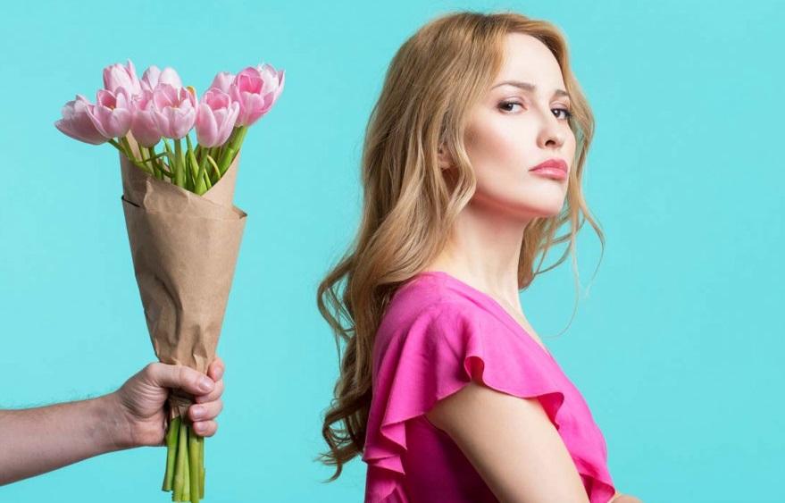 Femme qui tourne le dos à un bouquet de fleurs