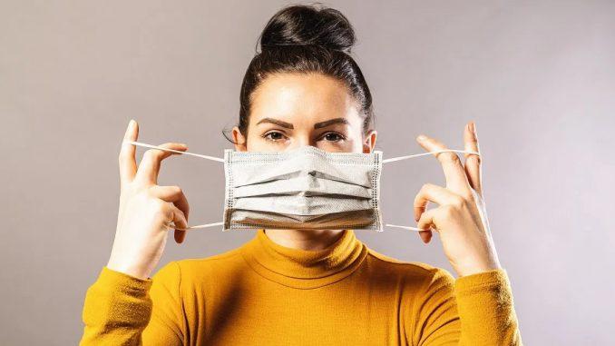 Femme mettant un masque sur son visage
